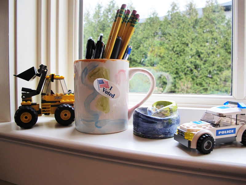 "Child's Window Sill, with an ""I Voted"" sticker on a mug."